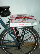 Medium-sized boxed pizza strapped to a rear cargo rack.